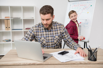 freelancer working with laptop while his son drawing on flipchart at office