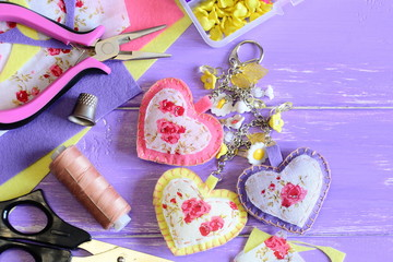 Decorative hearts keychain. Handmade felt and fabric keychain on bag or backpack. Summer accessory for women or girls. Crafts and craft supplies background. Top view