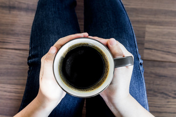 Woman's hand holding a cup of hot coffee