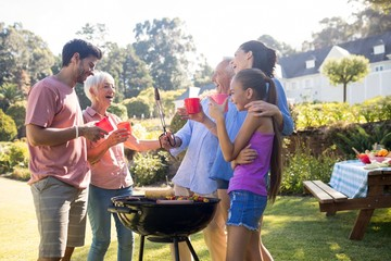 Fond de hotte en verre imprimé Grill, Barbecue Family laughing and talking while preparing barbecue in the park