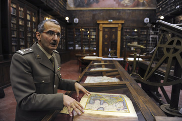 Head of Italy's Military and Geographic Institute General Colella shows an old map book in Florence