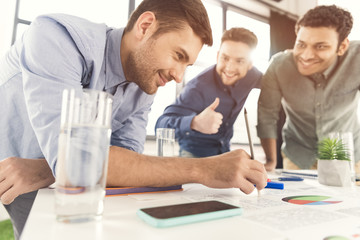 Three young businessmen leaning at table and working at project together, business teamwork concept