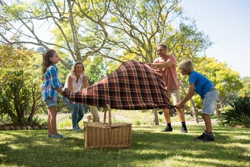 Family spreading the picnic blanket