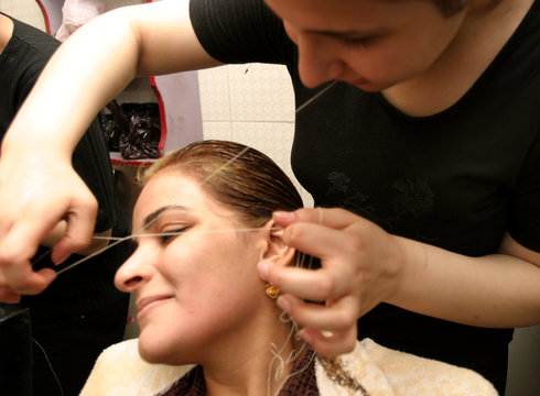 An Iraqi bride-to-be gets undergoes a hair removal technique called 'threading' at a beauty parlor i..