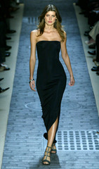 A model for designer John Varvatos walks the runway in a black strapless evening gown during the pre..
