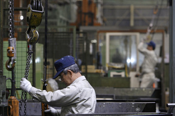 A worker operates machinery at a factory in Moriya