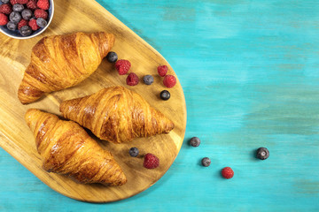 Crunchy French croissants with fresh raspberries and blueberries