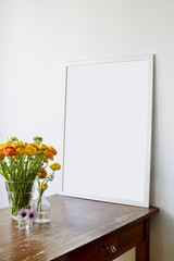 large frame on used wooden table with buttercup flowers