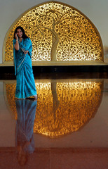 A woman talks on a mobile as she stands near a wood carving at a hotel lobby in New Delhi June 8, 20..