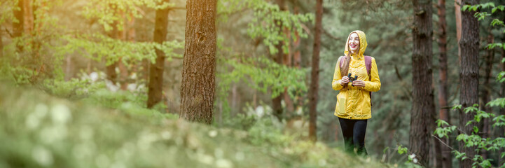 Landscape view on the pine forest with woman hiking in yellow raincoat. Cropped image for wide format
