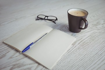 Pen and book with coffee cup on table