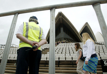 A SECURITY GUARD WATCHES PEDESTRIANS AROUND THE FOOTSTEPS OF SYDNEY'SOPERA HOUSE.