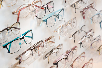 Shelf with many pairs of glasses in opticians shop