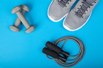 Sport shoes, dumbbells and skipping rope on blue background. Top view. Fitness, sport and healthy lifestyle concept.