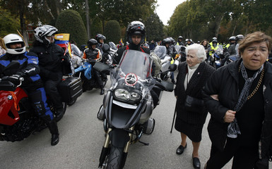 An elderly woman walks through a group of bikers gathering for the start of the International caravan for the release of hostages in Madrid