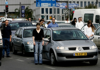 Israelis stand next to  their cars as traffic stops in Tel Aviv
