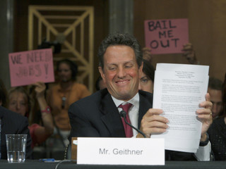U.S. Treasury Secretary Tim Geithner concludes his testimony as protest signs are raised behind him in Washington