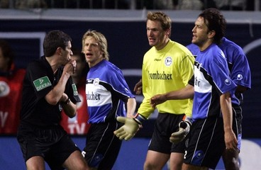 Arminia Bielefeld's Kauf, Hain and Schuler argue with referee Merk during their German Cup ...