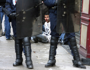 A youth with blood on his face sits behind French riot police after being apprehended in Paris