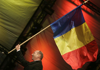 Romania's President Basescu carries the national flag after a speech during New Year celebrations in Bucharest