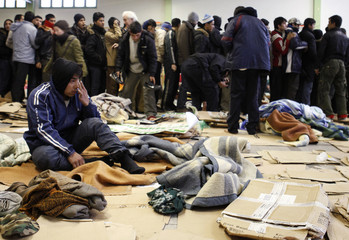 Afghan wakes up others wait for food distribution after they slept in gymnasium converted into shelter in northern France