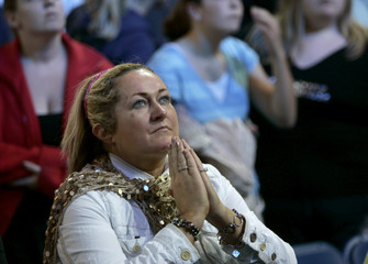 A member of the audience watches a childhood movie of Princess Diana at the Concert for Diana at Wembley Stadium in London