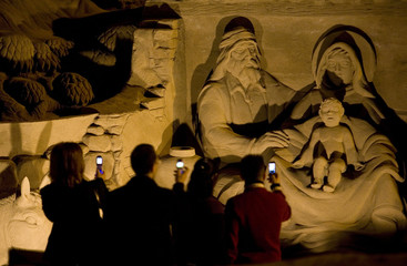 People take pictures with their mobile phones of a sand sculpture which depicts Christian nativity scene at Las Canteras beach in Spain's Canary Island of Gran Canaria