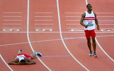 ENGLAND'S DWAIN CHAMBERS GRIMACES IN PAIN AS TEAM MATE LEWIS-FRANCISLIES ON THE TRACK DURING THE MEN'S ...