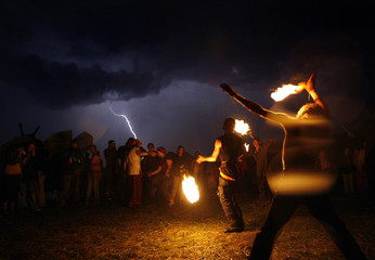 People attend an arts and music festival during a thunderstorm near the village Bardino