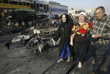 A woman cries as she and her family walk past the scene of bomb attacks in Baghdad