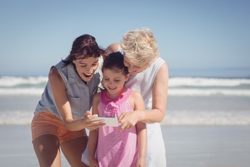 Happy multi-generation family using mobile phone at beach