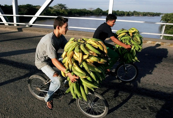 -PHOTO TAKEN 09DEC04- Children riding bicycles carry bananas on a bridge over the Arauca river, at t..