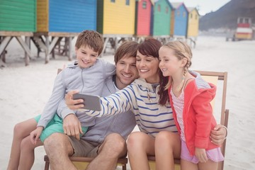Smiling family taking selfie at beach