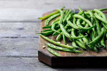 Green beans on wooden cutting board. Copy space