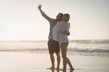 Young couple taking selfie on shore at beach