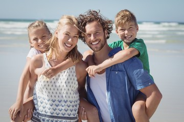 Portrait of happy family piggybacking at beach