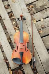 Скрипка и смычок на деревянном фоне с осенними листьями