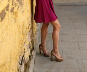 Молодая девушка в летнее платье позирует на улице
