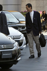 A man looks at Honda cars outside a showroom in downtown Tokyo