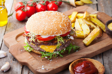 Burger, hamburger, french fries on a cutting board