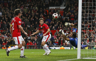 Manchester United's Owen and Neville watch as Besiktas' Recber makes a save during their Champions League soccer match in Manchester