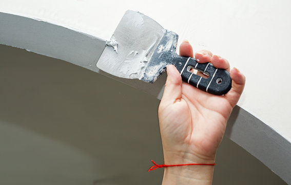 Worker working manual with wall plastering tools inside a house