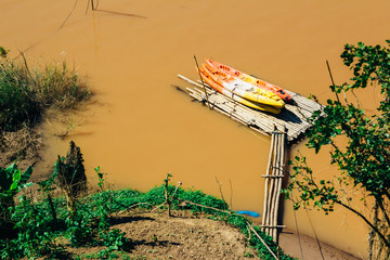 Kayak boats in orange-yellow muddy Ou river, Nong Khiaw, Laos
