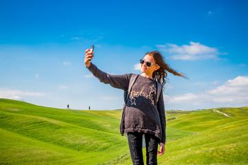 Fillette faisant un selfie  devant les Paysages du Val d'Orcia en Toscane