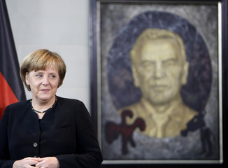 German Chancellor Merkel stands next to a portrait of former Chancellor Schroeder in Berlin