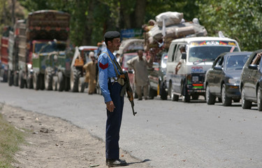 A policeman stands guard as dozens of vehicles line up at a check-point in Bari Kot to return by road to the Swat Valley
