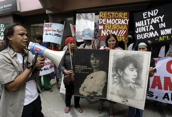Activists hold posters of pro-democracy opposition leader Kyi, during a small rally calling for peace and democracy in Myanmar, outside the building housing the Myanmar Embassy in Makati City