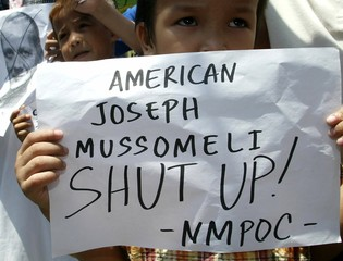Filipino Muslim children hold a placard beside a picture of U.S. embassy Charge d' Affaires ...