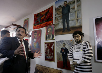 Anti terrorist police officer Marco Castro talks to reporters next to a statue of Abimael Guzman, the jailed leader of Peru's Shining Path rebels, at a police museum in Lima