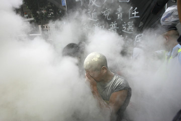 A pro-democracy protester protects himself as police use fire-extinguishing powder in Hong Kong